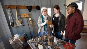 Colonial re-enactor Ruth Claussen, of Annapolis, talks to visitors Kaylee Weatherford, of Crofton, and Megan Coggins, of Bowie, at Hogshead. (Steve Ruark / Capital Gazette)
