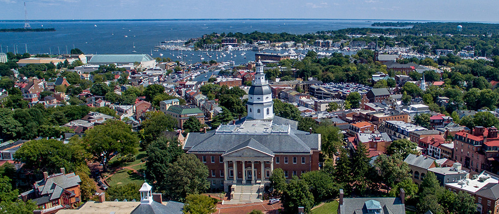An aerial view of the City of Annapolis with the Maryland State House in the foreground, with buildings, trees, and the waterfront in the background.